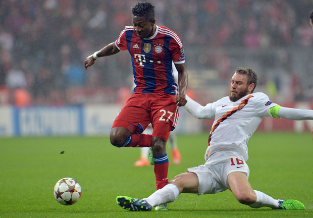Bayern's David Alaba, left, and Roma's Daniele De Rossi challenge for the  ball during the Champions League group E soccer match between Bayern Munich  and ...
